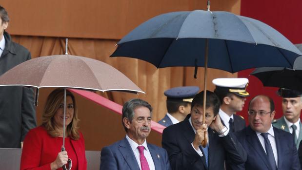 Susana Díaz y Javier Fernández, ambos con paraguas, el miércoles en el desfile de la Fiesta Nacional