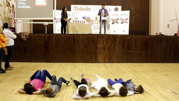 Unos niños, tumbados, escuchan el discurso de los premios Domus