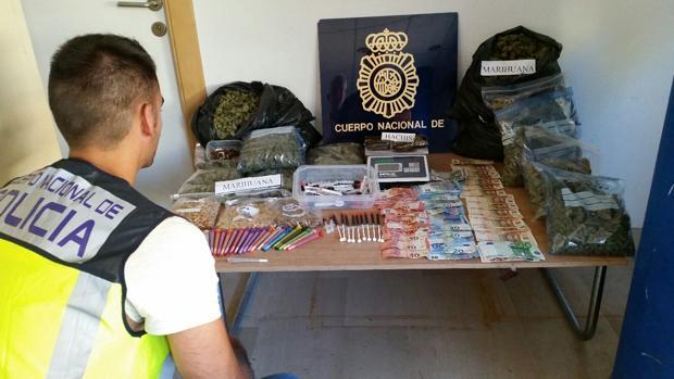 Un agente obxerva el material incautado en el registro al club de fumadores ilegal en Alicante