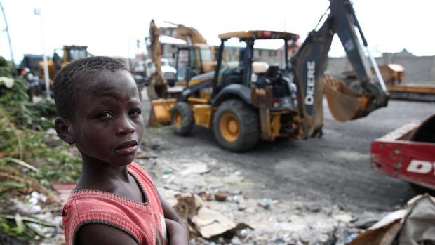 Un niño haitiano, ante las máquinas que trabajan en la reconstrucción de las zonas devastadas por el huracán