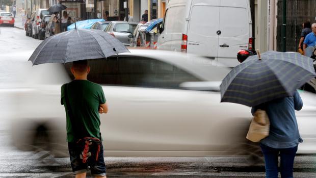 Dos personas se resguardan de la lluvia en el centro de Valencia