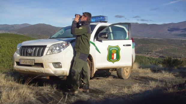 Un agente medioambiental junto a un vehículo oficial con los rotativos instalados