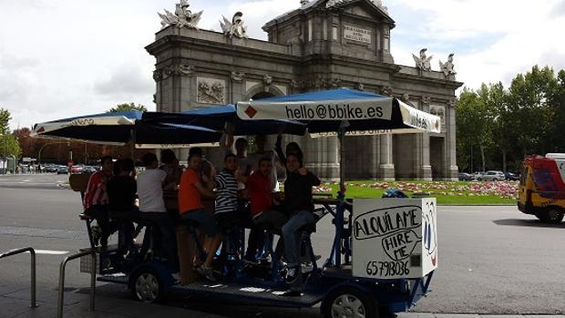 Unos de los vehículos a pedales, a su paso por la Puerta de Alcalá