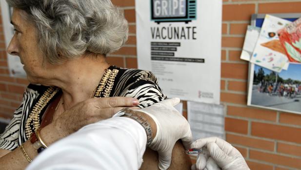 Una mujer recibe la vacuna contra la gripe en un centro de salud de Valencia