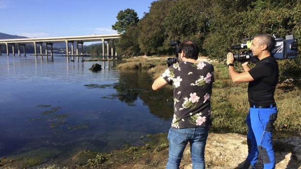 Dos reporteros fotografían la zona de Taragoña donde apareció el móvil de Diana Quer