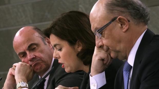 Soraya Sáenz de Santamaría, acompañada por los ministros de Economía y Competitividad y de Hacienda, Luis de Guindos (i) y Cristóbal Montoro