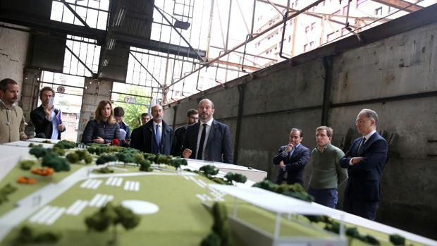 El consejero de Transporte y Vivienda, Pedro Rollán, con responsables de Metro y cooperativistas, ante la maqueta del plan para soterrar las cocheras de Cuatro Caminos, presentado en las propias cocheras