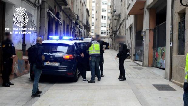 Los agentes introducen en el vehículo a uno de los arrestados por el asalto al cura en Vigo