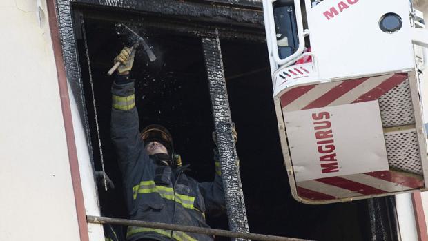Un bombero retira restos con riesgo de desprendimiento en la ventana de la vivienda incendiada
