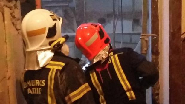Los bomberos municipales acceden al interior de la vivienda, en la calle Lagasca