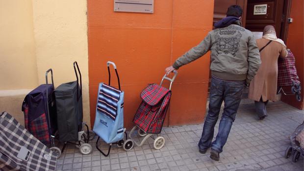 Personas necesitadas haciendo cola en un centro benéfico de reparto de alimentos, en Zaragoza