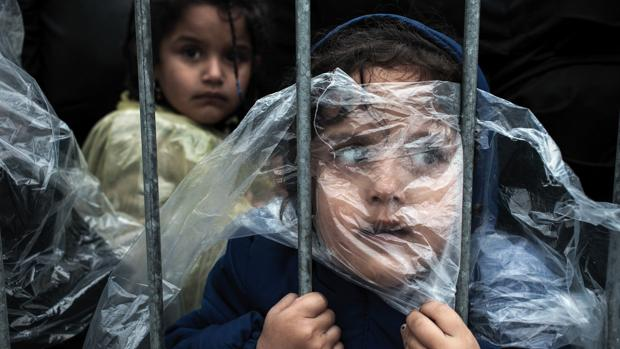 Niños refugiados tapados con plásticos esperan su turno para registrarse en Preševo, Serbia