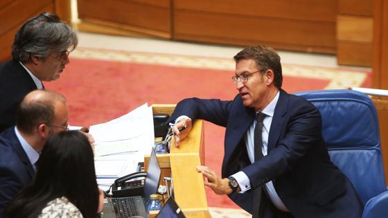 Feijóo charla desde su escaño con el portavoz del grupo del PPdeG, Pedro Puy