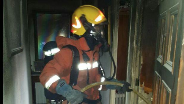 Un bombero trabaja en la extinción del fuego en el interior de la vivienda en Canals