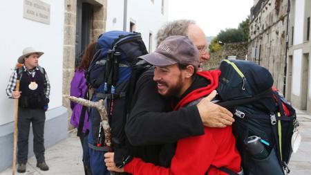 Dos peregrinos se abrazan tras terminar el Camino en Santiago