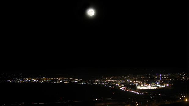 La superluna este lunes por la noche y, debajo, el Polígono de Toledo; la imagen está tomada desde la Biblioteca del Alcázar de Toledo