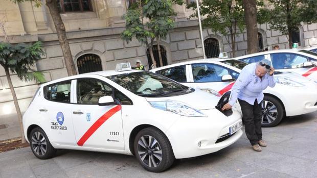 Una conductora uniformada muestra el punto donde se enchufan a la red los nuevos taxis eléctricos