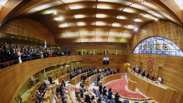 Diputados e invitados en la tribuna de público cantan el himno gallego durante la apertura de la Legislatura