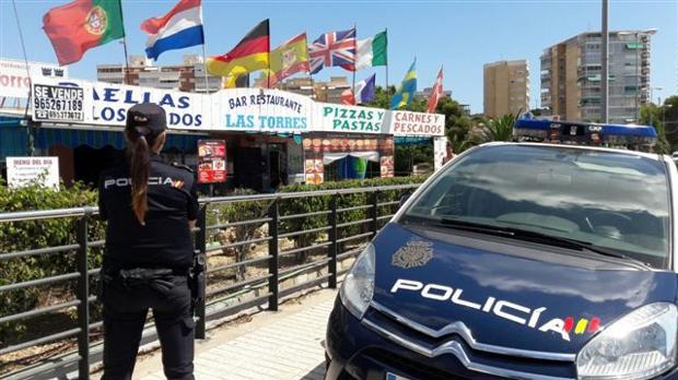 Una agente de la Policía Nacional junto a un coche patrulla