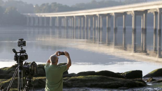 Un hombre fotografía el puente de Taragoña, cerca de donde se halló el móvil de Diana Quer