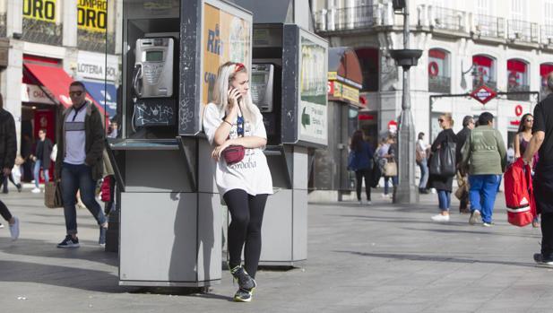 Una joven habla por el teléfono móvil, apoyada en una cabina de la Puerta del Sol