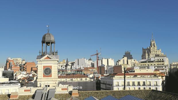 El reloj de la Puerta del Sol, sobre los tejados del centro de Madrid