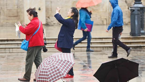 Varias personas se protegen de la lluvia, este martes, en Valencia