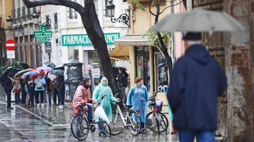 Varias personas se resguardan de la lluvia, este martes, en Valencia