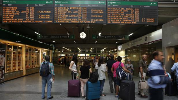 Viajeros miran los horarios en la estación madrileña de Atocha