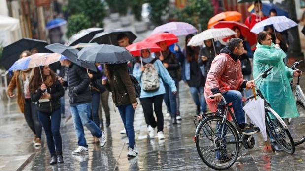 Transeúntes se protegen de la lluvia este martes en la ciudad de Valencia