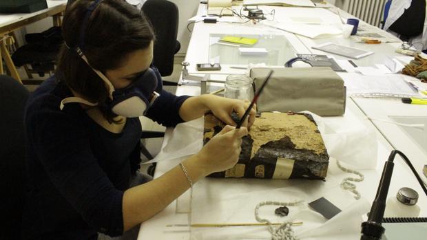 Los restauradores, en pleno trabajo de recuperación de uno de los libros históricos