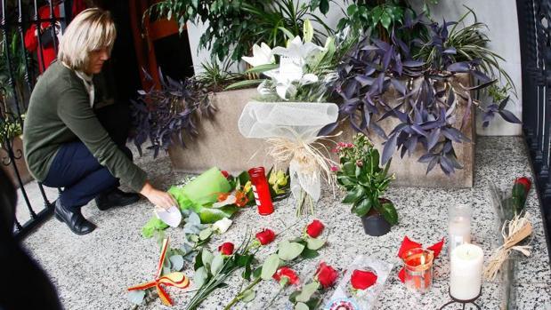 Una mujer deja un ramo de flores en el portal de Rita Barberá