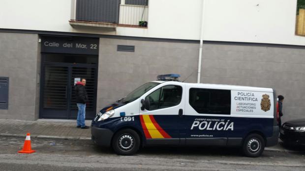 Un coche de la Policía Científica, junto a la vivienda en la que se ha producido el parricidio