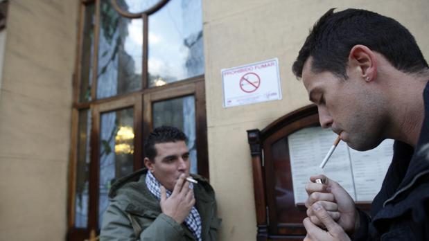Dos hombres fuman en una calle de Madrid