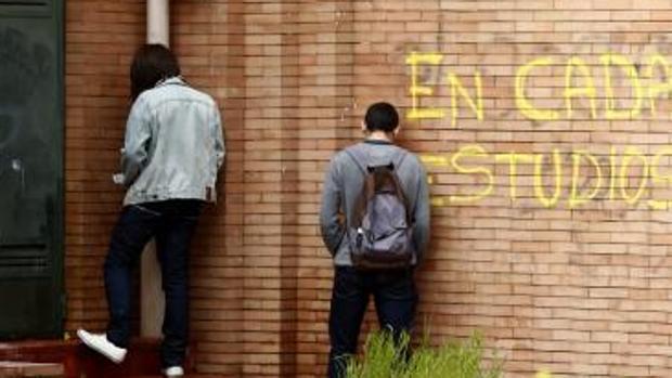 Dos jóvenes orinan en una pared de un edificio madrileño