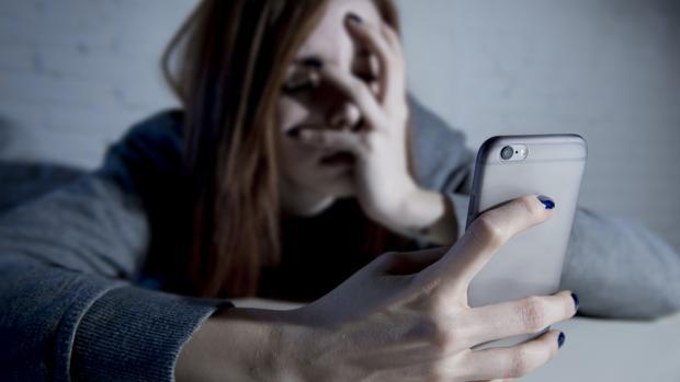 Una adolescente observa, atemorizada, su teléfono móvil