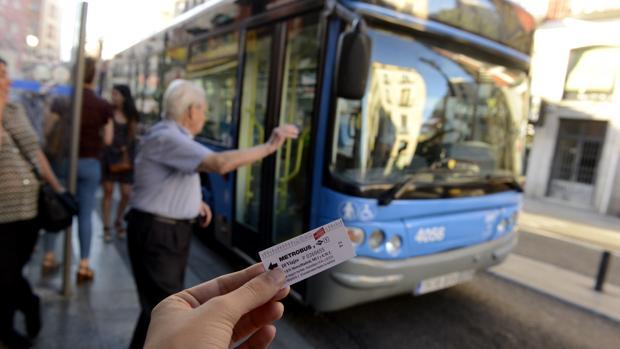 Un usuario muestra un billete de Metrobus, ante un autobús de la EMT