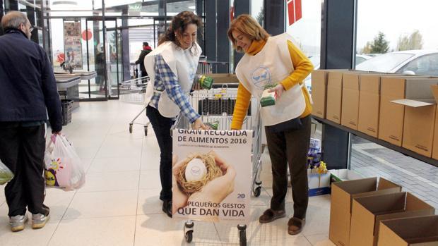 Dos voluntarias colocan alimentos en un carro de la compra