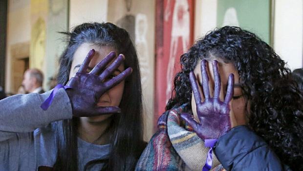 Dos adolescentes gallegas se cubren el rostro con las manos pintadas de violeta durante un acto por el 25 de noviembre en un instituto