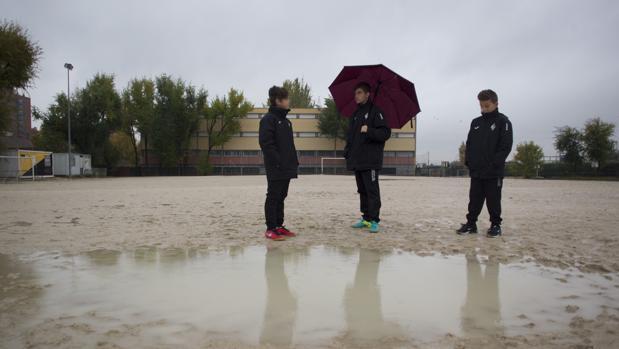Jugadores del Alzona, sobre el campo de fútbol, en un día de lluvia