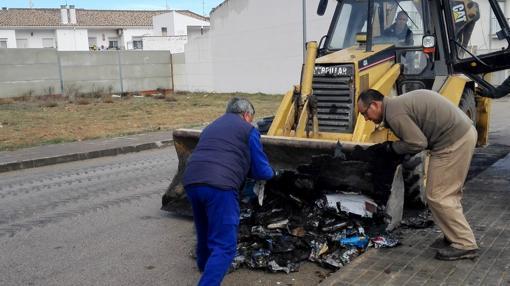Operarios municipales retiran los restos de un contenedor incendiado