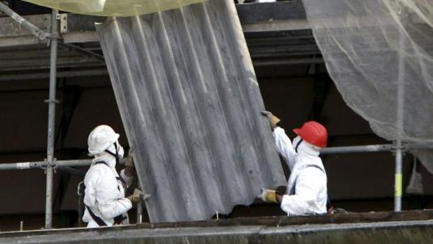 Dos operarios quitan una placa de uralita con fibrocemento