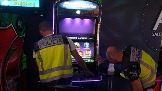 Dos agentes inspeccionan una de las máquinas manipuladas con descargas eléctricas