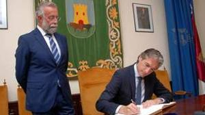 El ministro de Fomento, Íñigo de la Serna, firma en el libro de honor de Talavera de la Reina en presencia del alcalde, Jaime Ramos