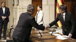 El nuevo conseller de Interior, Joaquim Forn, saluda a Puigdemont en la toma de posesión