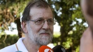 El presidente del Gobierno, Mariano Rajoy, atiende a los medios de comunicación durante su paseo por las orillas del río Umia