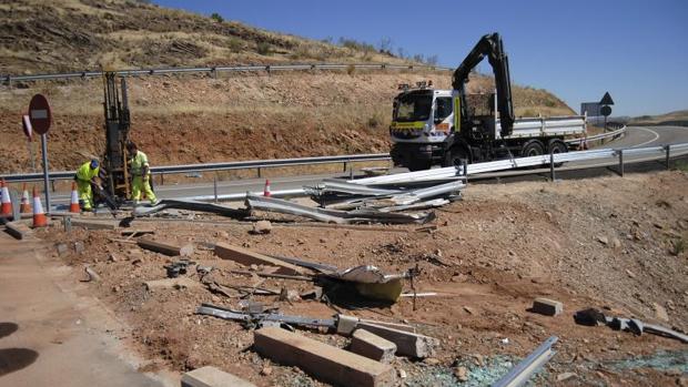 Operarios del servicio de mantenimiento de carreteras arreglan los guardarrailes afectados por el vuelco
