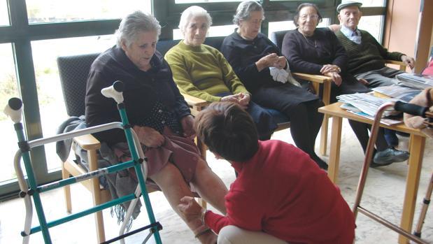 Una cuidadora atiende a un grupo de ancianos en el ayuntamiento orensano de A Veiga