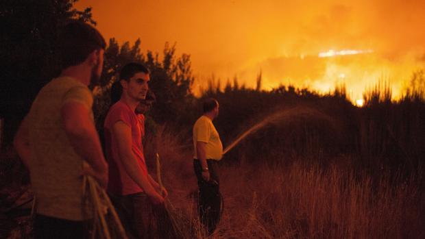 Vecinos de Vilardevós, en la comarca de Monterrei, combaten las llamas durante la noche