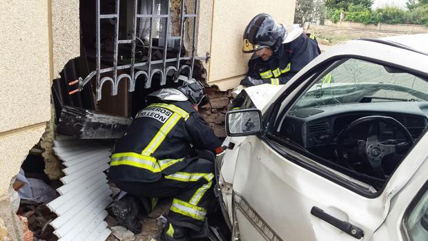 Los bomberos intervienen para sacar el coche y establizar la casa contra la que se ha emptrado en Matilla de la Vega (León)
